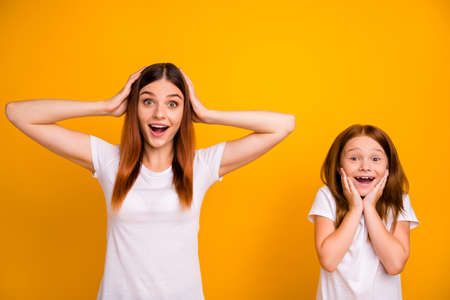 Portrait of astonished mommy and her kid with long hairstyle screaming touching head face wearing white t-shirt isolated over yellow background
