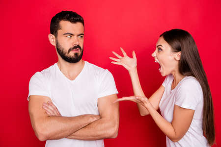 Photo of quarreling trendy two people couple with girl going mad having burst out shouting at guy not understanding while wearing white t-shirt enduring while isolated over red background