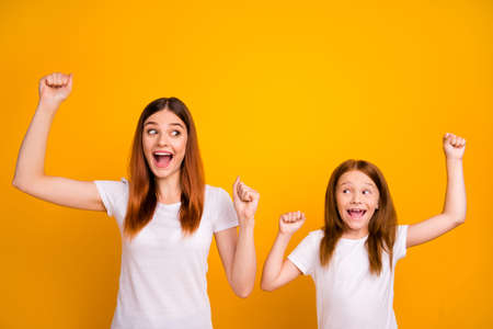 Portrait of cheerful mom and her kid with long hairstyle screaming wow omg wearing white t-shirt isolated over yellow background