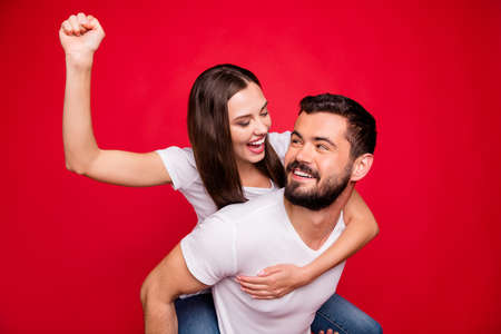 Photo of spouses together trendy casual piggyback pretending to be rider and mount while wearing jeans denim white t-shirt while isolated with red background Stock Photo