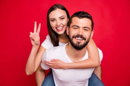 Photo of two funny trendy casual fooling piggyback nice cute people together loving each other wearing jeans denim white t-shirt while isolated over red background Reklamní fotografie