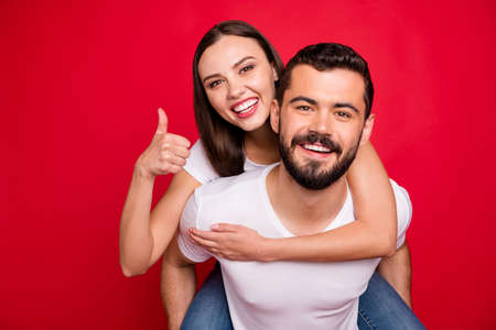 Photo of two trendy cheerful cute nice charming piggyback lovely cute beautiful handsome people wearing jeans denim fooling funky funny isolated with red background Stock Photo