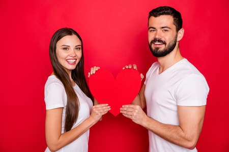 Photo of lovely nice cute charming couple of two people together holding heart with their hands wearing white t-shirt while isolated with red background Stock Photo
