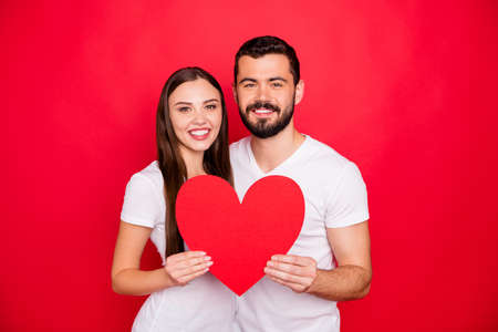 Photo of couple of two casual stylish charming trendy fascinating people couple together showing you big heart symbolizing their love while isolated with red background