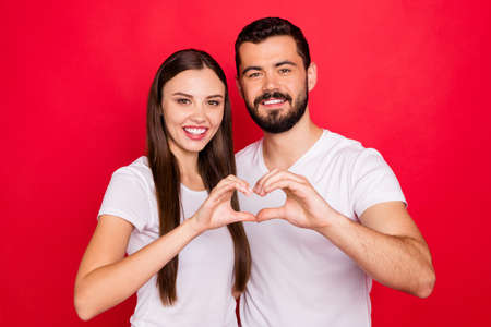 Photo of charming casual stylish cute lovely fascinating pretty spouses two people showing heart shape with their hands while isolated with red background