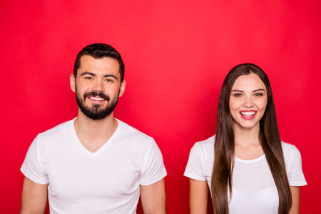 Photo of charming cute nice handsome beautiful couple looking at you while isolated with red backgroung with white t-shirts