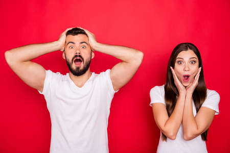 Photo of two stylish trendy funny funky cheerful overjoyed people wearing white t-shirts rejoicing with shopping mall discounts while isolated over red background