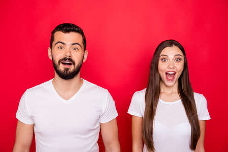 Photo of couple of two excited funny rejoicing ecstatic trendy brunet people overjoyed with something impossible while isolated over red background wearing white t-shirts