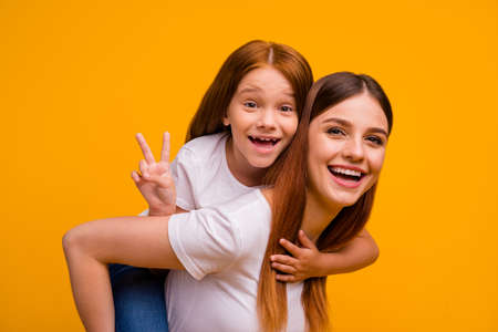 Close-up portrait of two nice-looking attractive lovely cheerful cheery glad playful person having fun free time holiday weekend showing v-sign isolated over bright vivid shine yellow background Stock Photo