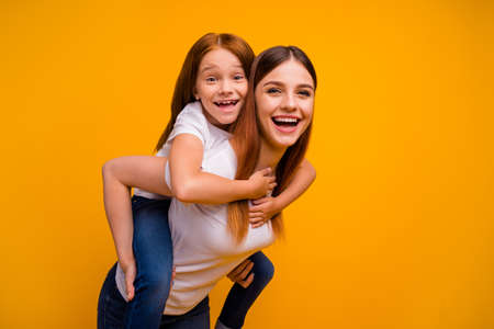 Close-up portrait of two nice attractive lovely cheerful cheery playful person mommy having fun free time piggy backing isolated over bright vivid shine yellow background 版權商用圖片