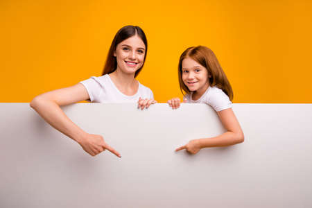 Portrait of two nice attractive lovely cheerful cheery confident person showing ad advert solution board present new novelty isolated over bright vivid shine yellow background