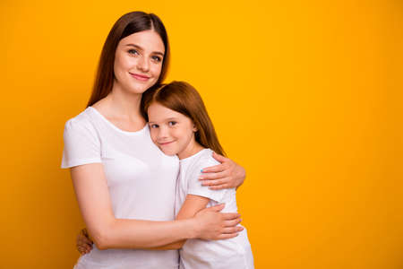 Portrait of two nice cheerful cheery tender gentle sweet dreamy person cuddling mommy mum spending time isolated over bright vivid shine yellow background