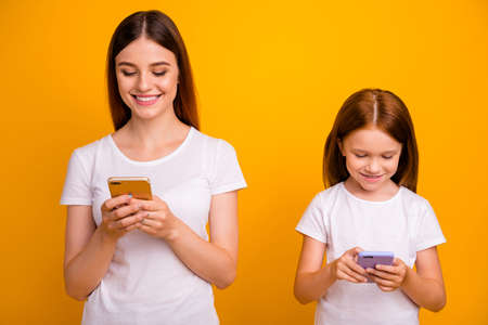 Portrait of cheerful people with ginger hair using modern technology wearing white t-shirt isolated over yellow background