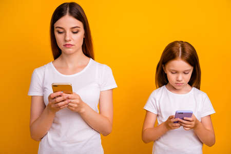 Portrait of concentrated people with foxy haircut using device wearing white t-shirt isolated over yellow background
