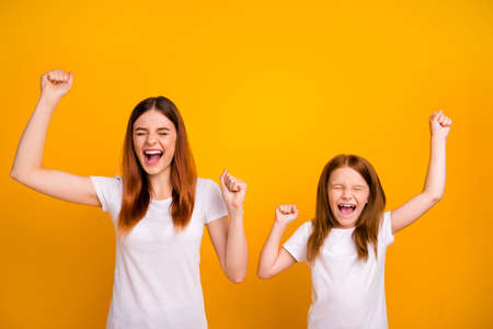 Portrait of delighted woman with long hair closing eyes raising fists screaming yeah wearing white t-shirt isolated over yellow background Stock Photo
