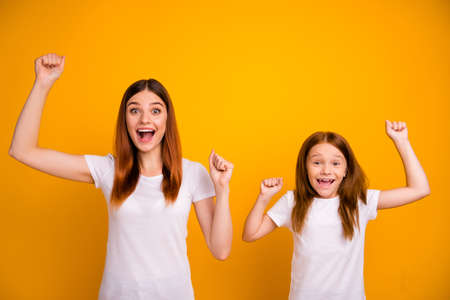 Portrait of crazy lovely people with long haircut raising fists screaming wow omg wearing white t-shirt isolated over yellow background Stock Photo