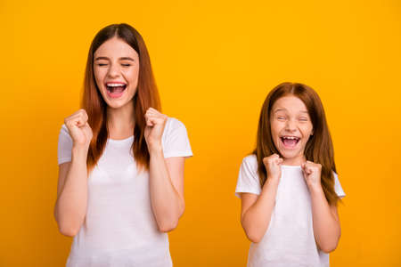 Portrait of cheerful crazy people with long hair screaming raising fists wearing white t-shirt isolated over yellow background