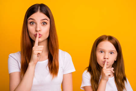 Close up photo of cute people with long ginger hair saying hush wearing white t-shirt isolated over yellow background