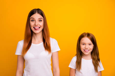 Portrait of pretty mom with her kid having long hair fooling isolated over yellow background