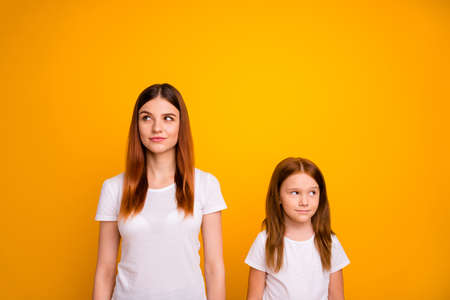 Portrait of minded ladies with long haircut looking having thoughts isolated over yellow background