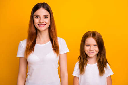 Portrait of charming ladies looking at camera with beaming smile isolated over yellow background