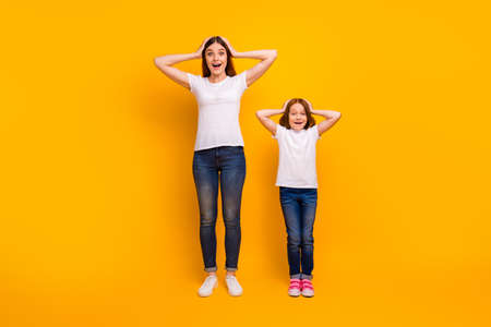 Full length photo of cheerful ladies with long haircut touching their head screaming wow omg isolated over yellow background