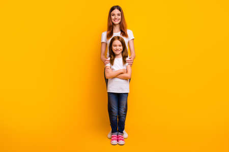 Full size photo of charming ladies with long hairstyle looking at camera with toothy smile isolated over yellow background Stock Photo