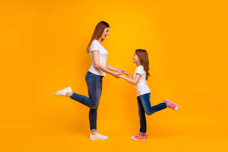Full length profile side photo of pretty mom with her kid having long hairstyle smiling wearing white t-shirt isolated over yellow background Stock Photo