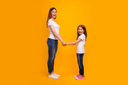 Full size profile side photo of impressed mom holding her child having long foxy hairstyle screaming wearing white t-shirt isolated over yellow background