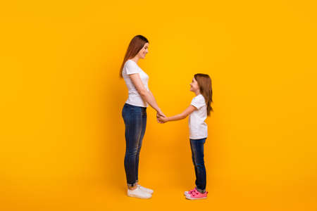 Full length profile side photo of lovely mommy with her kid having long haircut holding hands isolated over yellow background