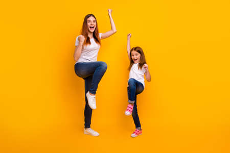Full length photo of lovely people with long hair raising fists wearing white t-shirt denim jeans isolated over yellow background