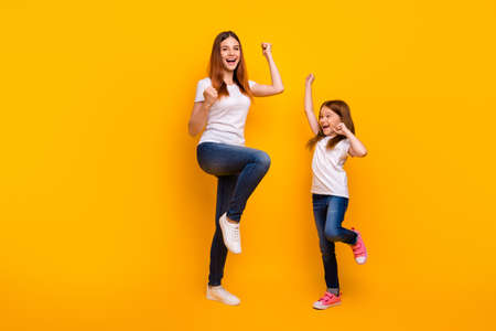 Full size photo of cheerful people with long hair raising fists screaming yeah wearing white t-shirt isolated over yellow background