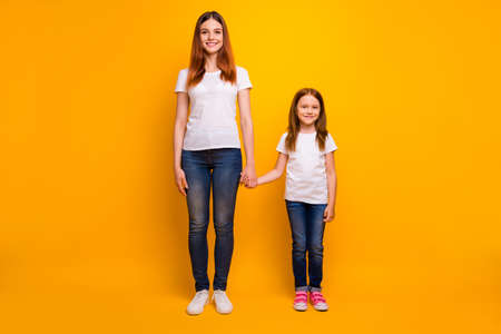 Full size photo of cheerful ladies holding hand smiling wearing white t-shirt denim jeans isolated over yellow background
