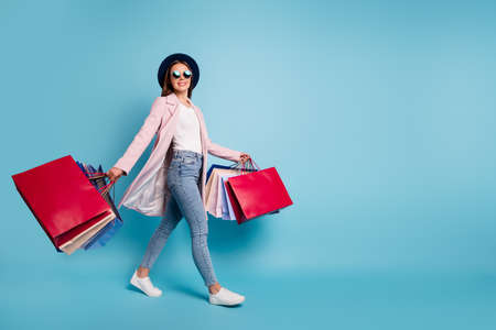 Full size photo of cute pretty cheerful lady in eyeglasses eyewear go shopping for bargains wear season cote denim jeans isolated over blue background Stock Photo