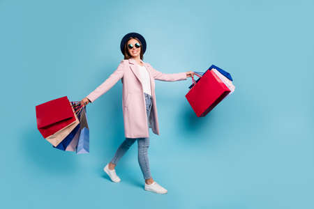 Full length photo of lovely cheerful lady in eyeglasses eyewear have rest go shopping buy souvenirs wear topcoat denim jeans isolated over blue background