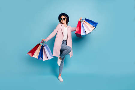 Full body photo of enthusiastic candid lady in eyewear eyeglasses go shopping buy purchases wear pink coat denim jeans isolated over blue background
