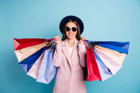 Portrait of cute candid lady in eyewear eyeglasses go shopping have many bags off enjoy her rest wear pink coat isolated over blue background