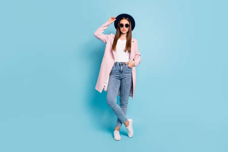 Full size photo of charming classy worker in eyeglasses eyewear touch her modern cap ready to decide work decision wear topcoat denim jeans isolated over blue color background