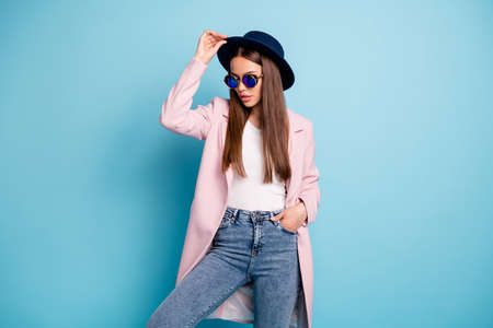 Portrait of charming stylish lady posing showing her fashionable retro outfit having free time wearing pink topcoat denim jeans isolated over blue background Stock Photo