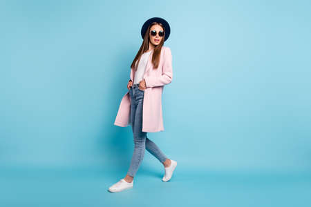 Full length photo of cute charming lady walking having promenade wearing pastel color topcoat denim jeans isolated over blue background Stock Photo