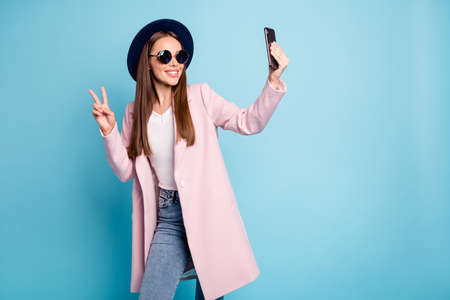 Portrait of cute content blog girl in eyewear eyeglasses making v-sign taking selfie having fun wearing pink stylish vercoat topcoat denim jeans isolated over blue background