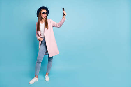 Full size photo of childish girl using her cell phone taking self photo having fun wearing eyeglasses eyewear topcoat denim jeans isolated over blue background