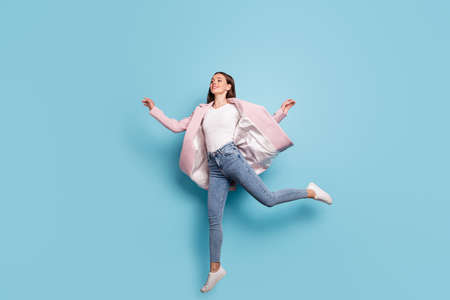 Full length photo of charming cute girl jump run for bargains on her holiday wear pink topcoat denim jeans isolated over blue background Stock Photo