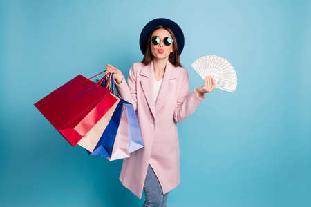 Portrait of lovely brown haired girl go shop with jackpot cash earnings prepare for valentine day send air kisses wear pink coat eyewear cap hat eyeglasses denim jeans isolated over blue background Фото со стока
