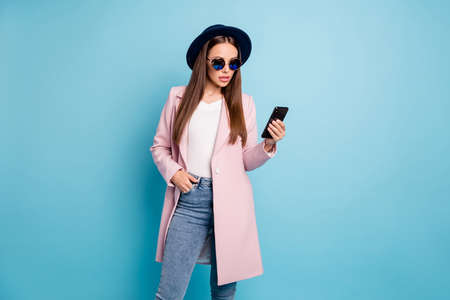Portrait of astonished woman use her cellphone read news wonder say its omg wear pink coat outfit stylish denim jeans eyewear eyeglasses isolated over blue color background