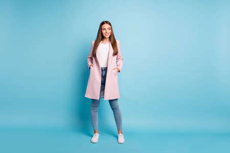 Full length photo of cool lady in good mood wear pastel color demi-season coat and jeans isolated blue background