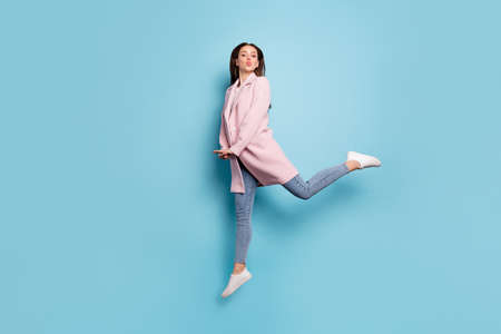 Full body photo of charming lovely girl jump have date send air kiss to her sweetheart wear season coat denim jeans isolated over pastel color background Фото со стока