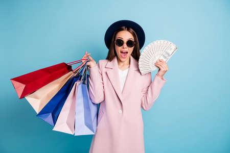Portrait of amazed funky millionaire girl scream omg have profit can shop all day wear stylish trendy coat eyewear eyeglasses isolated over blue color background Stock Photo
