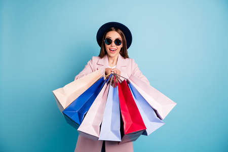 Portrait of astonished surprised lady in eyewear eyeglasses go shopping have incredible discount scream wow omg wear pink coat isolated over blue color background