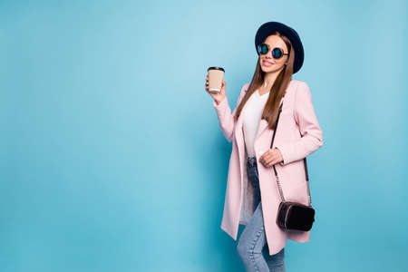 Portrait of cute sweet lady in eyewear eyeglasses hold mug with hot latte have free time stroll wear vintage coat denim jeans isolated over blue background